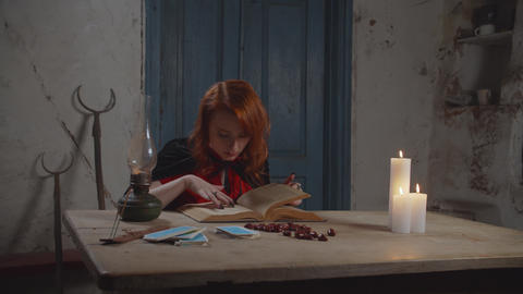 Concentrated white witch reading magic book indoor Live Action