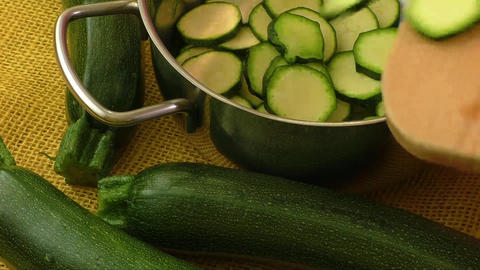 Cut zucchini on chopping stainless steel pot for cooking. Healthy food Live Action