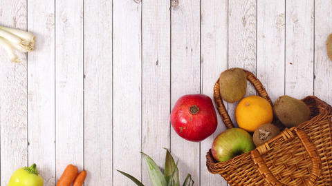 Fresh fruits and vegetables and wooden basket appear on wooden theme. Stop motion Live Action