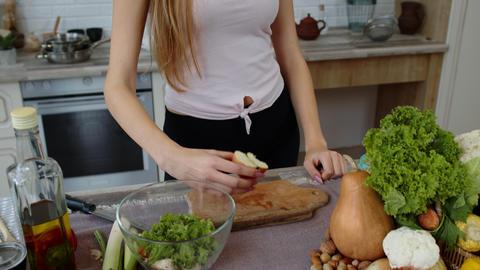 Vegan girl eating juicy apple. Girl measuring with tape measure her slim waist Live Action