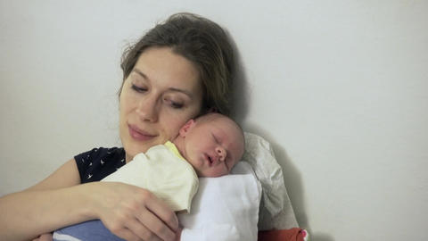 Mother At Home With Sleeping Newborn Baby Daughter Footage