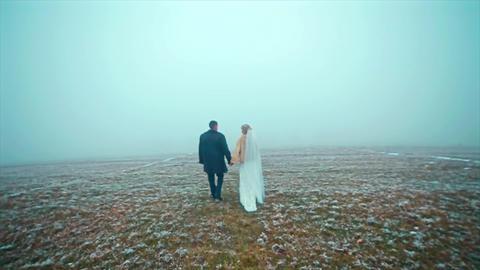 Wedding couple goes winter on Snowed Field Drone Footage