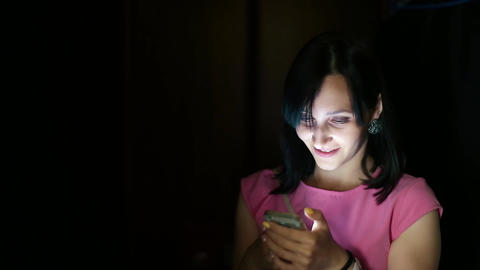 Girl with Beautiful Smile is Using Smartphone Footage