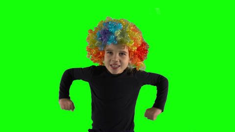 Angry girl with colorful clown wig looking at camera. Child negative emotion Live Action