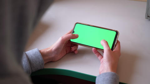 Woman's Hands are Holding Smartphone with Green Touchscreen on Table. Internet Live Action