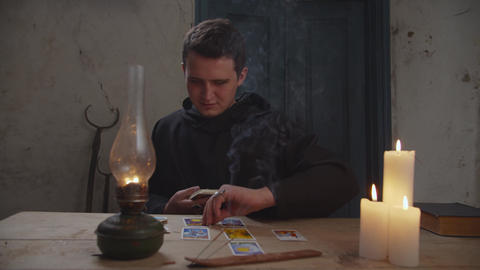 Black magician practicing tarot cards reading Live Action