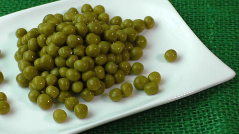 Green peas on a white plate Live Action