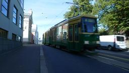 Light daytime traffic on Kanavakatu street, green tram rush towards and pass by Footage