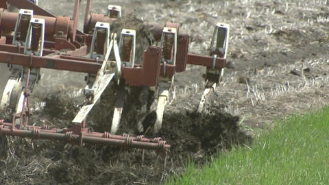 Tilling equipment being pulled through farm field Live Action