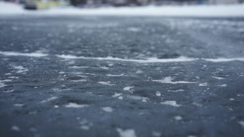 Closeup view on ice and snow road surface. Footage. Focus is on the road's Live Action