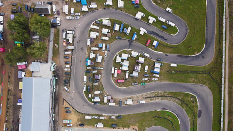 Aerial view of a winding road with cars parked on the side of the road Live Action