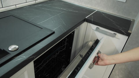 The woman opens the dishwasher and presses the power button. Female hand opens Live Action