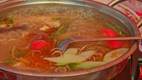Person Puts Ingredients into Boiling Fish Soup in Large Stew-pan Footage