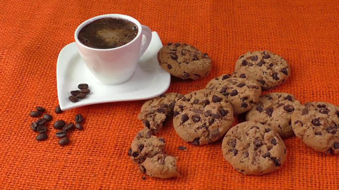 Chocolate chip cookies and cup of coffee shot on jute colored cloth Footage