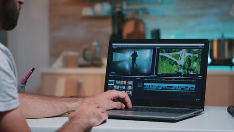 Videographer working remotely editing video footage Live Action
