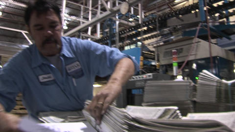 A worker stacks newspapers in the factory Footage
