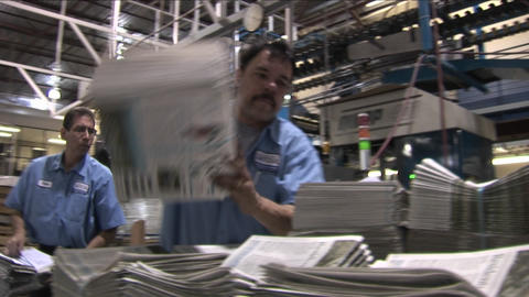 A worker stacks newspapers in the factory Stock Video Footage