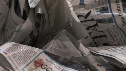 Old crinkled newspapers sit in a recycling bin in a factory Stock Video Footage