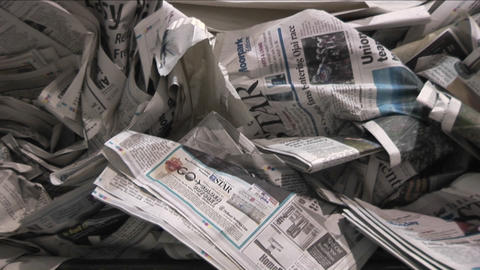 Old crinkled newspapers sit in a recycling bin in a factory Footage