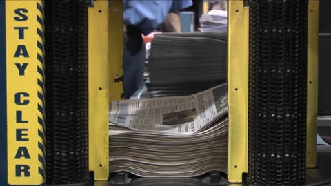 A machine stacks and binds newspapers in a factory Stock Video Footage