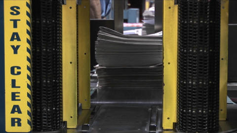 A machine stacks and binds newspapers in a factory Footage