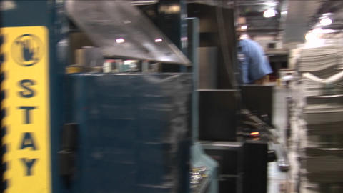 A machine stacks and binds newspapers in a factory then... Stock Video Footage