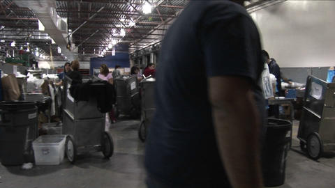 Pan across workers in a newspaper factory sorting and... Stock Video Footage