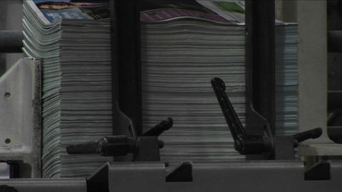 Magazine supplements are stacked in a newspaper factory Footage