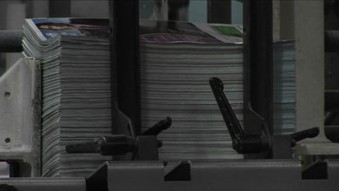 Magazine supplements are stacked in a newspaper factory Stock Video Footage
