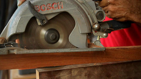 A person uses a circular table saw to cut through Stock Video Footage
