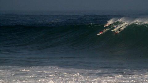 Multiple surfers ride very big waves in Hawaii Stock Video Footage
