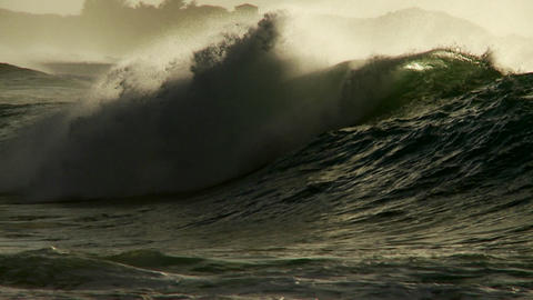 Large waves crest and break on a shoreline Stock Video Footage