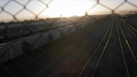 A time lapse shot through a chain link fence of a railway freight yard Footage