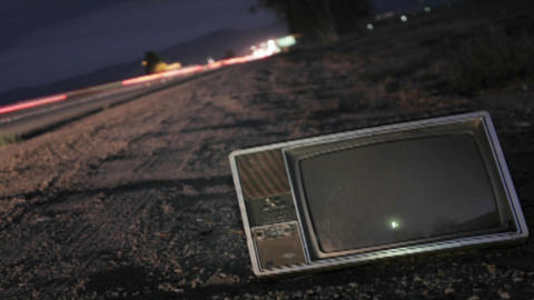 An abandoned TV set sits along a highway while traffic passes in time lapse Footage