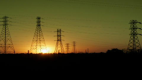 The sun sets behind high tension lines in this time lapse shot Footage