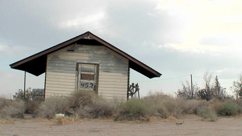 An old building stands abandoned in the desert Stock Video Footage