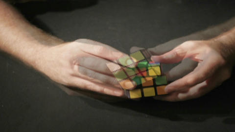 A time lapse shot of hands solving a Rubik's Cube puzzle Stock Video Footage