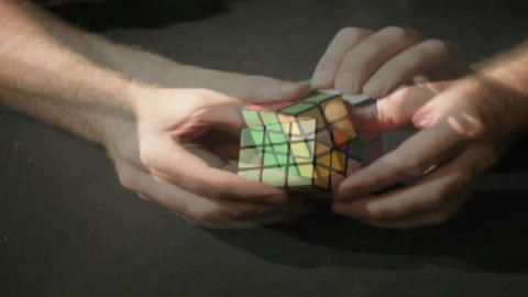 A time lapse shot of hands solving a Rubik's Cube puzzle Footage