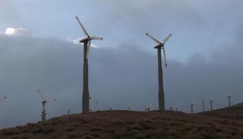 Windmills generate power on a hillside in california Stock Video Footage