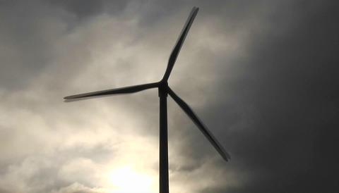 Backlit windmill generates electrical power on a hillside... Stock Video Footage