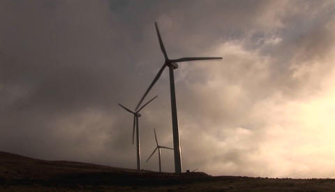 Backlit windmill generates electrical power on a hillside in California Footage