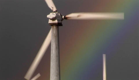 Tilt up to gorgeous rainbows illuminate wind powered generators spinning Footage