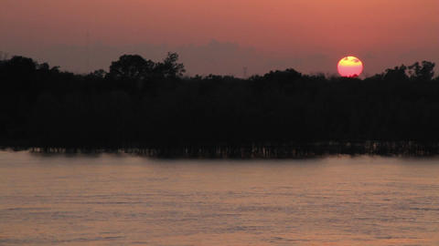 Wide shot sun setting over a river from the POV fr Stock Video Footage