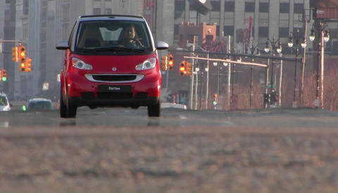 A man driving a red Smart car through a city Footage
