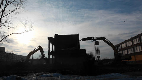A building is demolished and a plane flies overhead Stock Video Footage
