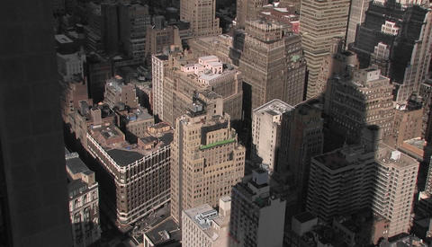 The Empire State Building's shadow falls on several smaller buildings below Footage