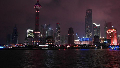 Boats travel across a cities water front area at night Stock Video Footage