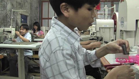 Asian youths sew in a factory Footage