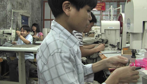 Asian youths sew in a factory Stock Video Footage