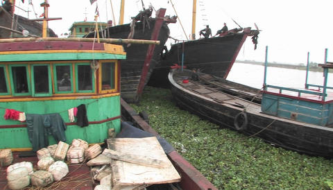 Fishing boats are moored at a dock, and fishermen prepare... Stock Video Footage